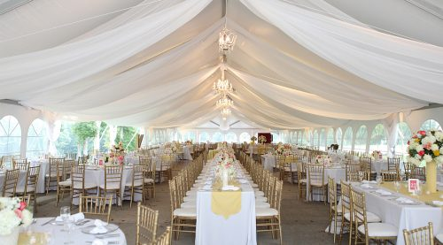 Daytime outdoor wedding under white canopy, square tables with gold chairs