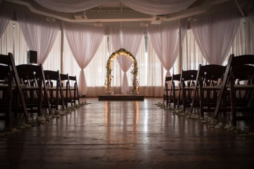 Beautiful wedding arch, lit up, large event hall, wood floor and chairs, dimly lit